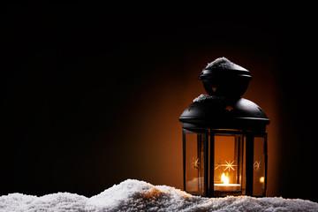 laterne in der dunkelheit steht im schnee