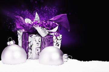 lila weihnachtsgeschenk im schnee mit christbaumkugeln