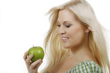 Hübsche blonde Frau isst einen Apfel