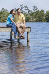 Romantic Man and Woman Couple Sitting By Lake