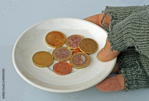 white saucer with coins inside held by a poor man