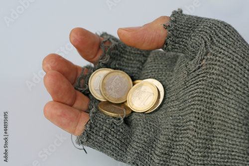 a poor man collects alms from a Euros in his glove