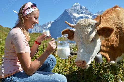 Girl with a jug of milk and a cow. Switzerland