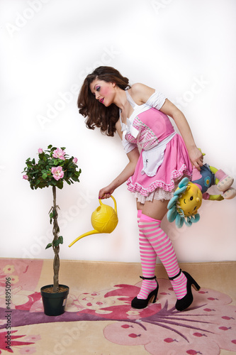 Cheerful beautiful girl with pink short dress watering flower in