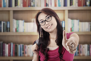 Student showing thumbs-up in library