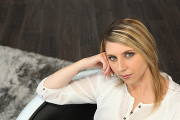 Blond woman sitting on a sofa