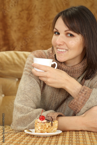 Pretty Caucasian woman sitting at a table with a cake