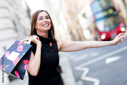 Shopping woman grabbing a taxi