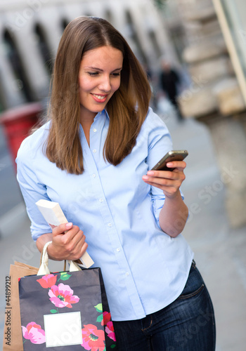 Shopping woman sending a text