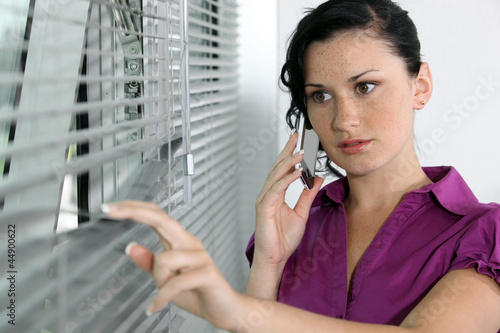 A brunette businesswoman peeping through the blinds.