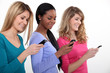 Three young women using their mobile telephones