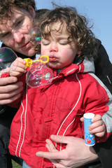 delightful toddler with daddy making soap bubbles