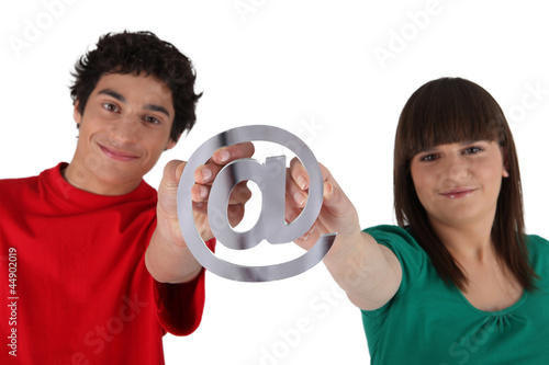 Teenagers holding at sign on white background