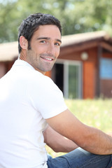 Young man sitting in front of chalet