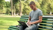 Young man with laptop sitting in the park, steadicam shot