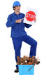 Man stood holding stop sign by crate of refuge