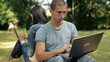 Young students with laptop and tablet in the park