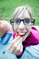 Young woman is eating strawberry