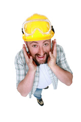 Goofy tradesman putting his hands along his face