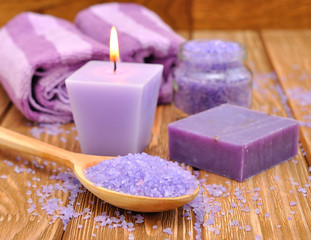 Purple sea salt and a burning candle