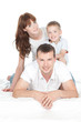 Smiling parents with little son lying on white background