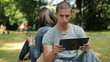 Young student with tablet computer in the park, steadicam shot