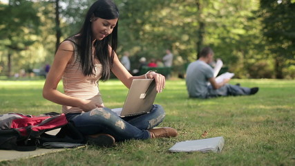 Young student with laptop relaxing in the park, steadicam shot