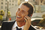 happy young businessman calling with mobile phone