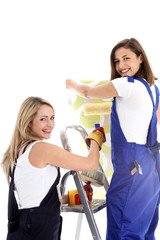 Two cheerful women at work wallpapering