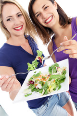 Two attractive women enjoying a healthy salad
