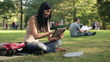 Young female student with tablet computer in the park