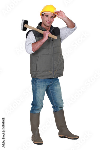 Tradesman carrying a mallet and wearing a hard hat