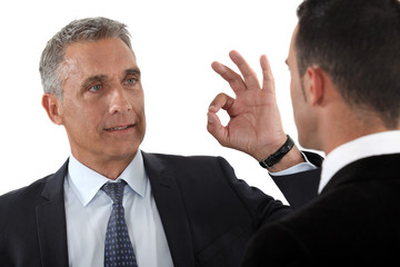 Man signaling to colleagues that everything is OK