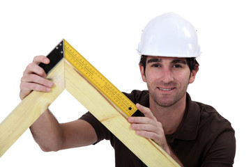 Man using setsquare on wooden frame