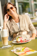 Cheesecake and latte cafe terrace woman sitting
