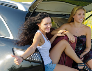 Happy women hitchhiking from back of car