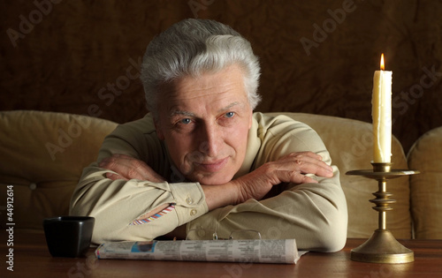 Beautiful Caucasian aged man sitting at a table
