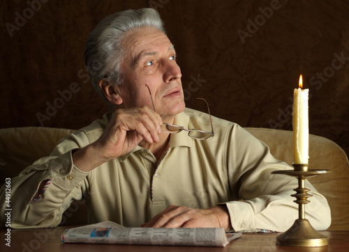 Beautiful Caucasian old man sitting at a table