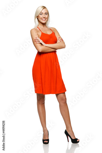 Full length of happy woman standing with her hands folded