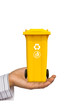 Hand offer yellow trash can