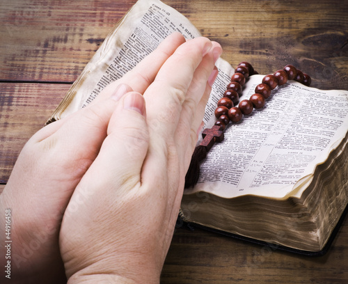 human hands holding the Bible and praying