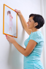 Woman hanging up photo of little girl
