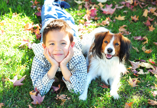 Young Boy and a Dog Lying on the Grass