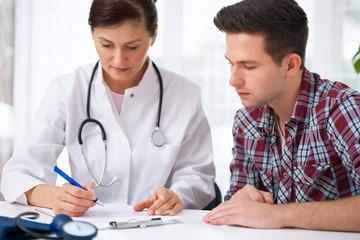 Ärztin berät einen jungen Patienten