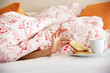 Woman's Hand Reaching From Under Duvet For Breakfast