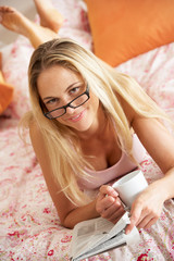 Pretty Woman Relaxing On Bed Reading Newspaper