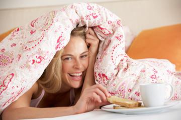 Pretty Woman Snuggled Under Duvet Eating Breakfast