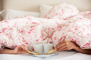 Couple's Hands Reaching From Under Duvet For Breakfast