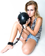 Woman holding prison ball attached to leg