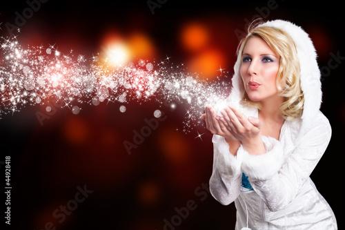 junge blonde Frau im Winteroutfit pustet Schnee